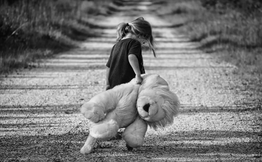 Criança sozinha de costas, com a cabeça baixa
