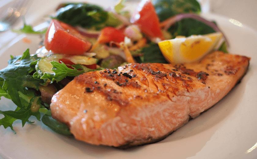 Um prato de comida com um filé de salmão e salada.