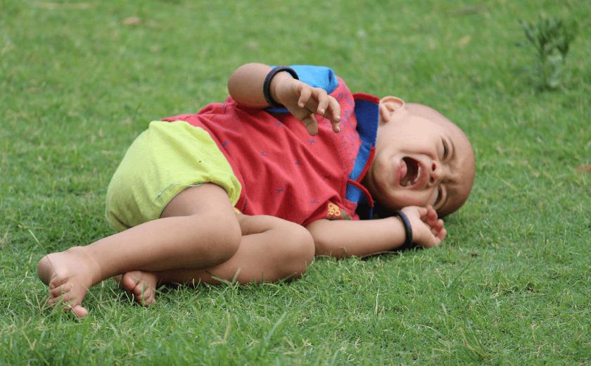 Um bebê deitado na grama chorando, fazendo birra