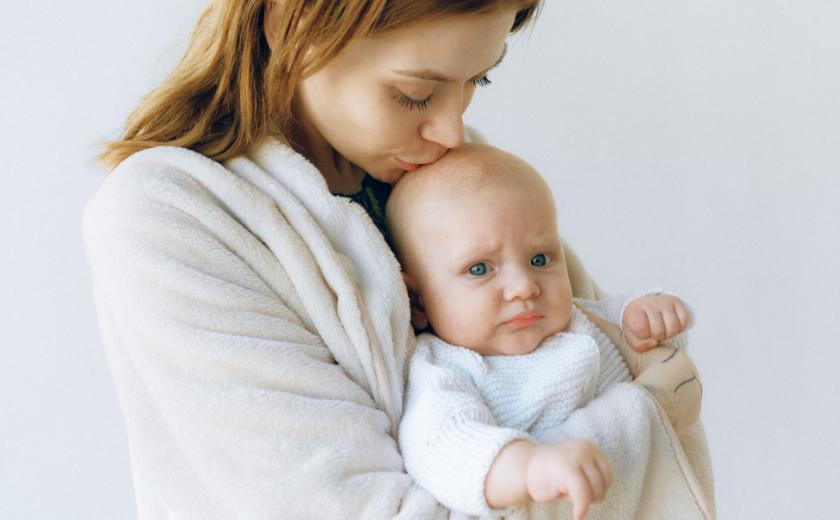 Mãe segurando o bebê com cólica