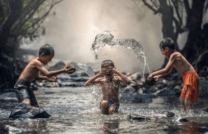 Três crianças brincando em um rio
