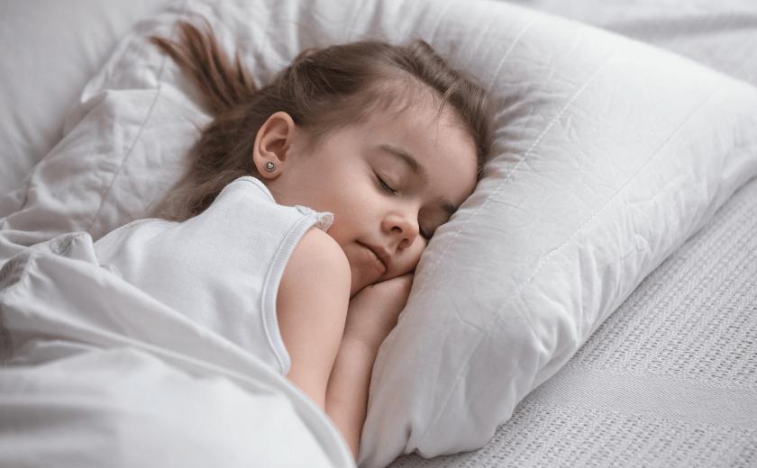 Criança dormindo tranquilamente, com a mão sob o rosto