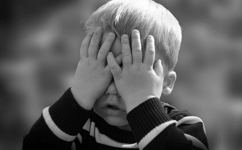 Criança tampando o rosto com as mãos