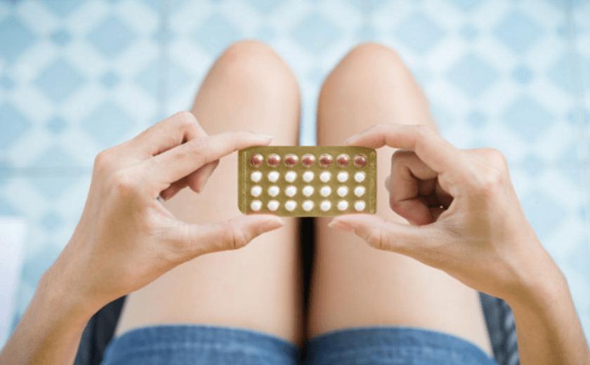 Uma mulher segurando uma cartela de pílulas anticoncepcionais