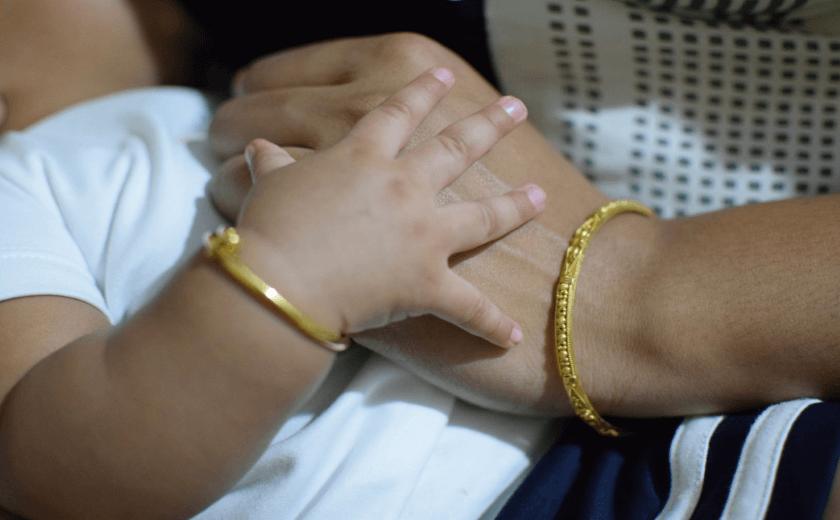 Mãe fazendo carinho nas mãos do filho