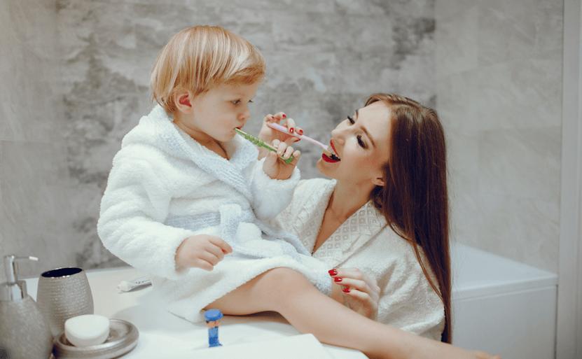 Mulher escovando os dentes do filho